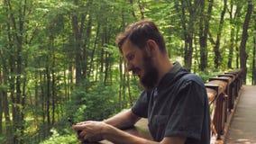 Um homem considerável com um smartphone está olhando na câmera e no sorriso vídeos de arquivo