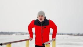 Um homem considerável novo em um revestimento e em uma calças preta de esportes no inverno em uma plataforma aberta executa o ots vídeos de arquivo