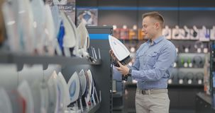 Um homem considerável novo examina o ferro na loja para comprar um apartamento novo avalia a usabilidade vídeos de arquivo
