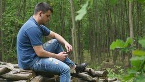 Um homem considerável novo nas madeiras escuta a música dos fones de ouvido Fotografia de Stock Royalty Free