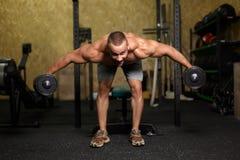 Um homem considerável que faz o bíceps ou o tríceps que levantam com pesos em um fundo do gym Poder, conceito dos esportes Copie  fotos de stock royalty free
