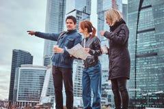 Um homem considerável que mostra a direção certa e o showplace aos turistas fêmeas na frente dos arranha-céus imagem de stock royalty free