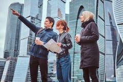 Um homem considerável que mostra a direção certa e o showplace aos turistas fêmeas na frente dos arranha-céus imagens de stock royalty free