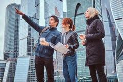 Um homem considerável que mostra a direção certa e o showplace aos turistas fêmeas na frente dos arranha-céus foto de stock royalty free