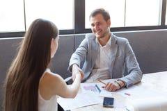 Um homem contínuo no escritório agita as mãos com a menina, para um bom trabalho imagens de stock royalty free