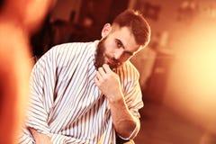 Um homem corajoso considerável com uma barba em um barbeiro Imagens de Stock