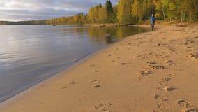 Um homem corre ao longo do lago em um Sandy Beach Cedo na manhã no alvorecer Joga esportes e conduz um estilo de vida saudável filme