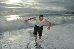 Um homem corre das ondas Foto de Stock