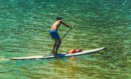 Um homem corssing o rio e está praticando o esporte do caiaque foto de stock