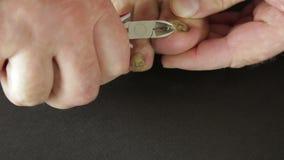 Um homem corta as unhas do pé contaminado com ferramenta do fungo vídeos de arquivo