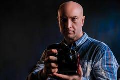 Um homem crescido em uma camisa com uma câmera em suas mãos imagens de stock royalty free