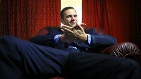 Um homem cruel em um terno senta-se em uma poltrona de couro, olha a câmera, gestos, linguagem corporal vídeos de arquivo
