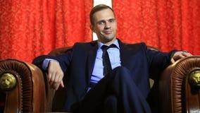 Um homem cruel em um terno senta-se em uma poltrona de couro, olha a câmera, gestos, linguagem corporal filme