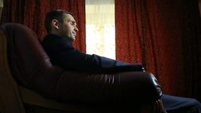 Um homem cruel em um terno senta-se em uma poltrona de couro, olha a câmera, gestos, linguagem corporal video estoque