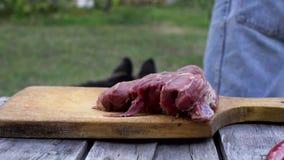 Um homem dá a um cão um a parte de carne ao cortar um bife video estoque