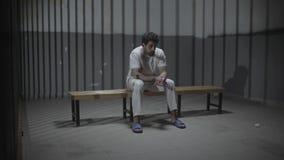 Um homem da preocupação que senta-se na prisão