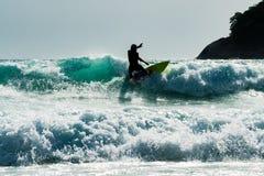 Um homem da silhueta do surfista que tem o divertimento que surfa sobre o wav azul grande Fotos de Stock