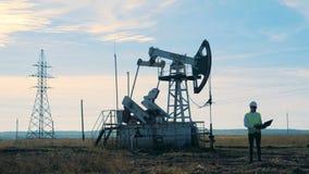 Um homem datilografa em um portátil perto da torre de óleo, fim acima filme