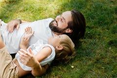 Um homem de cabelo escuro considerável com uma barba encontra-se com rapaz pequeno em um gramado verde no ar fresco e nos sorriso fotos de stock