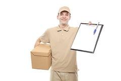 Um homem de entrega que traz um pacote Imagem de Stock Royalty Free