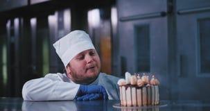 Um homem de fascínio do padeiro com uma baixa barba funde facilmente para fora as velas em um bolo de aniversário belamente decor video estoque