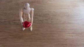 Um homem de madeira da boneca no dia de são valentim no assoalho de madeira com o ato do amor e da relação Imagens de Stock Royalty Free