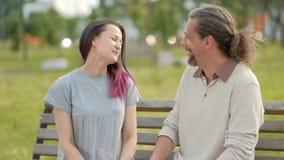 Um homem de meia idade atrativo relaxado com cabelo cinzento longo e uma jovem mulher com o cabelo tingido que abraça e que cumpr video estoque