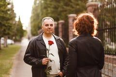 Um homem de meia idade dá uma rosa a uma mulher, data romântica imagem de stock