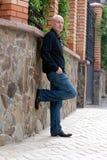 Um homem de meia idade pensativo está estando perto da parede de pedra foto de stock