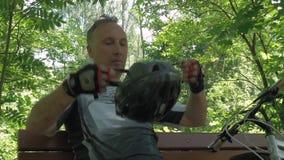 Um homem de meia idade que prepara-se para dar um ciclo Veste luvas especiais e um capacete filme
