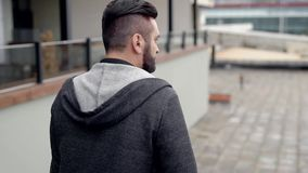 Um homem de negócio com uma pasta, andando através da cidade Um homem anda abaixo da rua no negócio vídeos de arquivo