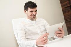 Um homem de negócio novo que sorri ao trabalhar a tabuleta - almofada de I Um cle foto de stock royalty free