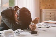 Um homem de negócio para fora forçado guarda sua cabeça no desespero imagem de stock