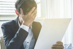 Um homem de negócio para fora forçado guarda sua cabeça no desespero imagens de stock
