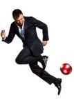 Um homem de negócio que joga a esfera de futebol de mnanipulação Fotografia de Stock