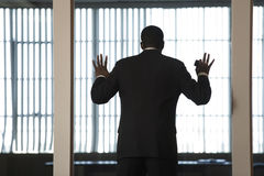 Um homem de negócio que olha para fora através de uma parede de vidro dentro Imagem de Stock Royalty Free