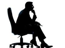 Um homem de negócio que senta-se na silhueta da poltrona Imagens de Stock