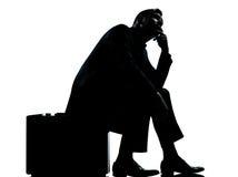 Um homem de negócio que senta-se na silhueta de espera da mala de viagem Imagens de Stock