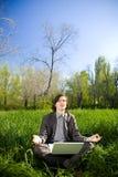 Um homem de negócio relaxa no campo de grama Imagens de Stock Royalty Free