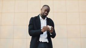 Um homem de negócios afro-americano novo perde todo o dinheiro Somente cem notas de dólar à esquerda video estoque