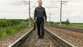 Um homem de negócios anda as trilhas railway vídeos de arquivo
