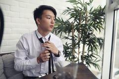 Um homem de negócios asiático novo está esperando um sócio em um café Bu fotografia de stock royalty free