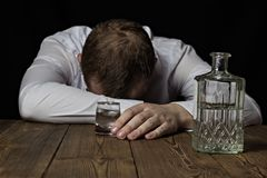 Um homem de negócios bêbado encontra-se em uma tabela, em sua mão um tiro do vinho com álcool, um fundo preto, alcoólico imagens de stock