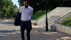 Um homem de negócios com barba em um casaco e camisa branca caminha no parque na estrada, olha para seu relógio na mão e decola filme
