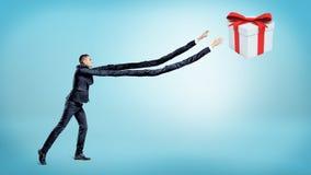 Um homem de negócios com os braços extremamente longos que tentam travar uma caixa de presente no fundo azul fotografia de stock