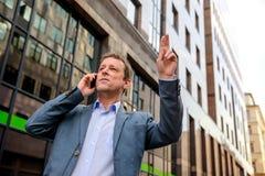 Um homem de negócios da Idade Média que acena para o táxi Imagens de Stock