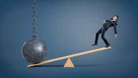 Um homem de negócios desequilibrado que está em uma balancê de madeira e overweighed por uma bola de destruição Fotos de Stock Royalty Free
