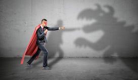Um homem de negócios do super-herói que luta fora uma sombra do dragão no fundo concreto foto de stock