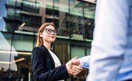 Um homem de negócios e uma mulher de negócios novos que agitam as mãos fotografia de stock