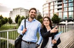 Um homem de negócios e uma mulher de negócios novos que andam em uma ponte imagem de stock
